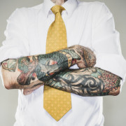 business man with rolled up sleeves showing tattoos on forearms